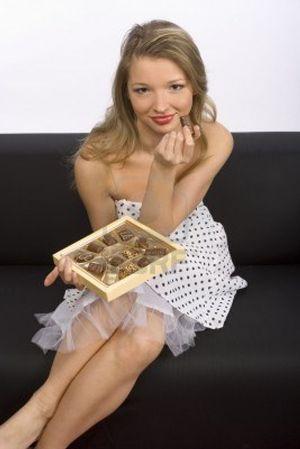 756987-joven-mujer-con-la-sesion-en-el-sofa-negro-con-caja-de-bombones